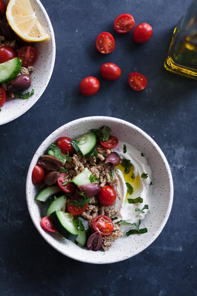 overhead shot of a bowl filled with plain greek yogurt, Mediterranean spiced ground turkey, sliced tomatoes, cucumbers and olives, fresh mint and a drizzle of olive oil