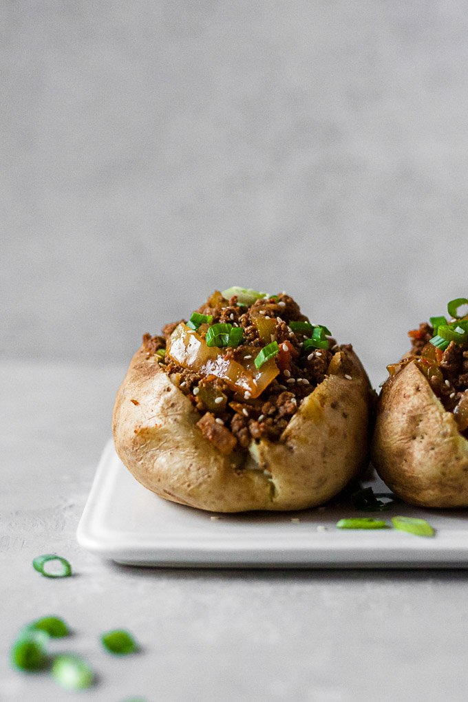 straight on shot of whole30 korean sloppy joe in baked potato on a white plate with scallions in the foreground