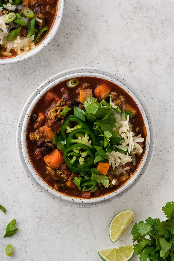 overhead shot of slow cooker turkey chili in bowl with cilantro limes and jalapeno