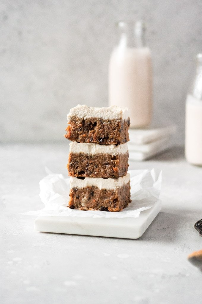 stack of three raw vegan carrot cake bars with cashew cream cheese frosting